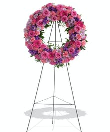 Pink and Purple Flowers arranged on a standing wreath display for the service in Baton Rouge LA