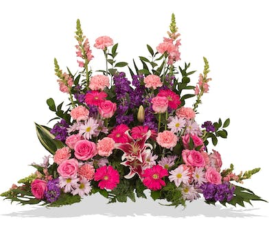 Pink and Purple Flowers arranged in a design to go on the floor in front of casket or cremation urn in Baton Rouge