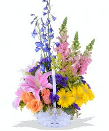 Mixed  spring flowers in white handle basket for Easter delivered baton rouge LA